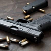 Gun with ammunition on dark background.