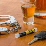 Schnapsglas mit Autoschlüssel, Alkoholtester und Handschellen