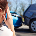 stressed driver sitting on roadside after car accident