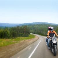 motorcyclist and passenger riding motorbike
