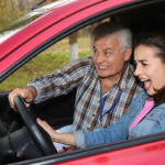 Young woman and senior instructor in car. Fail driving license exam