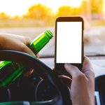 Man drinking behind the wheel holding a phone