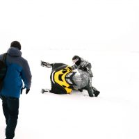 man falls off snowmobile