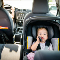 Mother and child strapped in rear-facing car seat in car