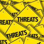 Yellow sign reads threats