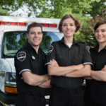 Group of three paramedics standing in front of ambulance