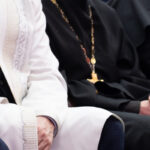 A Muslim mullah in white clothes and a Christian priest in a black cassock are sitting next to each other. The concept of religious cooperation, understanding, tolerance and friendship.