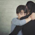 Sad child hugging his mother