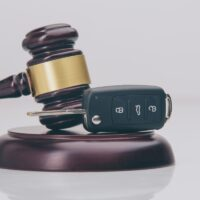Close-up Of Gavel And Car Key On Sounding Block Against Grey