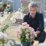 Man in black knelt at grave